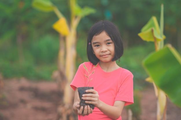 Дети, держащие посев дерева для посадки на почву