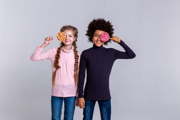 お菓子を持っている子供たち。一緒に立って、灰色の背景に立っている間キャンディーで遊ぶファンキーな小さな子供たち