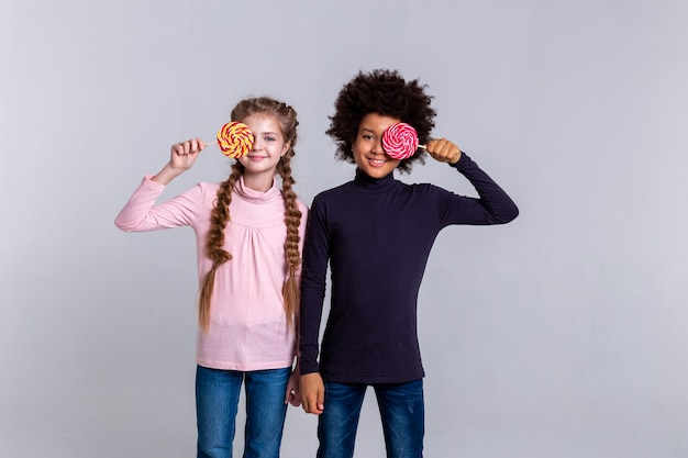 Kids holding sweets. funky little children standing together and playing with candies while standing on grey background