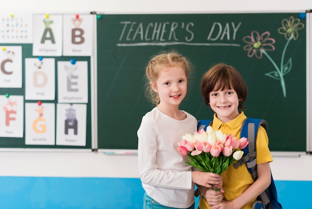 Kids holding together a bouquet of flowers for their teacher