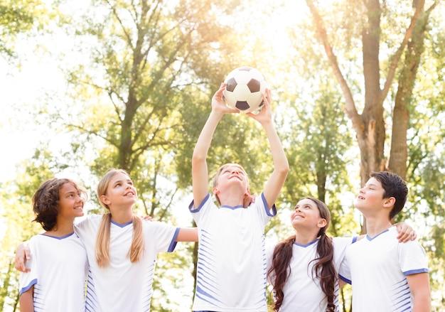 Bambini che reggono un pallone da calcio