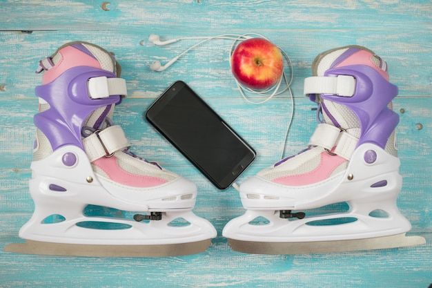 Kids ice skates with adjustable size and accessories on the wooden floor.