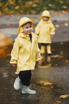 秋の公園の子供たち。黄色いレインコートを着た子供たち。屋外で楽しんでいる人。