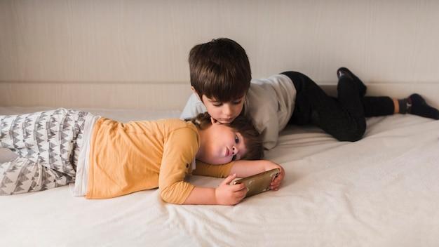 スマートフォンでベッドにいる子供たち