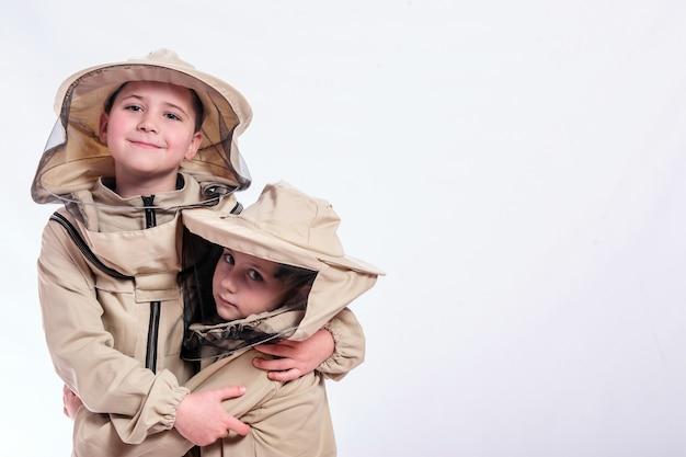 스튜디오 흰색 배경에서 포즈를 취하는 양봉가의 옷을 입은 아이들. 프리미엄 사진