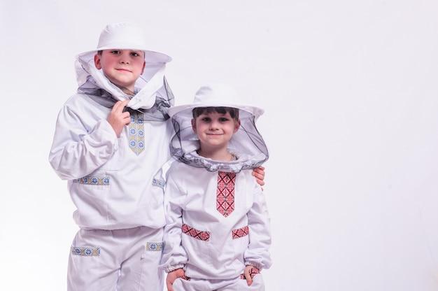 스튜디오 흰색 배경에서 포즈를 취하는 양봉가의 옷을 입은 아이들.
