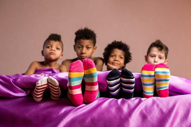 カラフルな靴下に座っている子供たち。ベッドの上の靴下の男の子。 1つの会社の4つの感情。それらのそれぞれが異なって感じます。