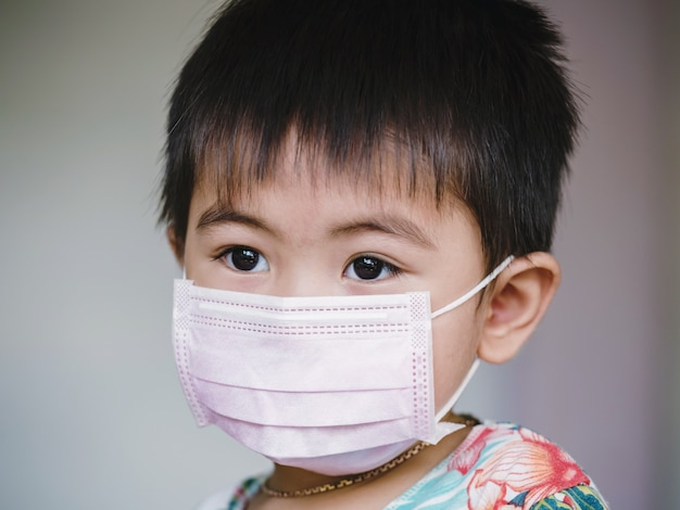 얼굴 마스크에 아이. 어린이는 코로나 바이러스와 독감 발생시 안면 마스크를 착용합니다. 바이러스 및 질병 보호