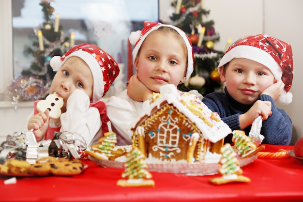 진저 브레드 하우스를 장식하는 산타 모자에있는 아이들 프리미엄 사진