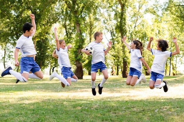 Дети в спортивной одежде прыгают на открытом воздухе