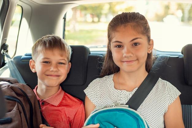 学校に行く途中の後部座席の子供たち