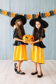 Kids in witch costumes holding halloween pumpkin