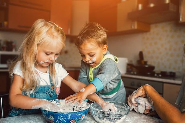 子供たちは台所で小麦粉で遊んでいます