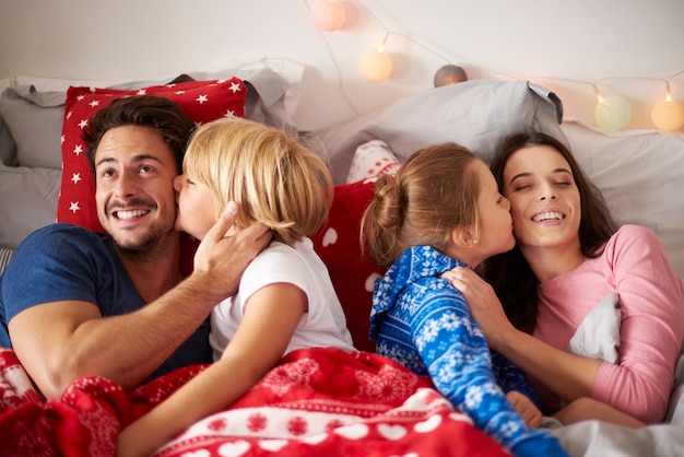 ベッドで両親にキスする子供たち