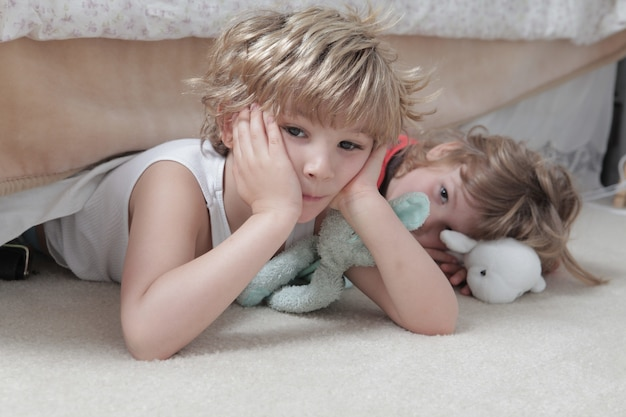 Kids laying on the floor with toys under the lights against a blurry background