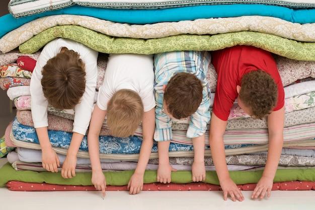 매트리스 더미 안에 누워 즐거운 시간을 보내는 아이들