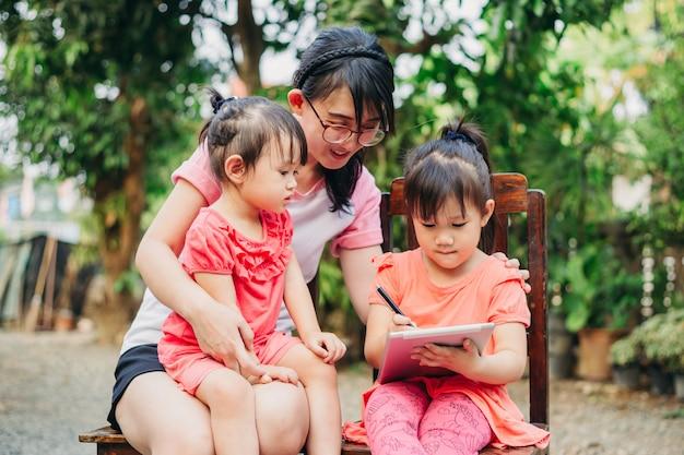 아이들은 태블릿을 사용하여 어머니와 함께 읽고 쓰는 법을 배웁니다.