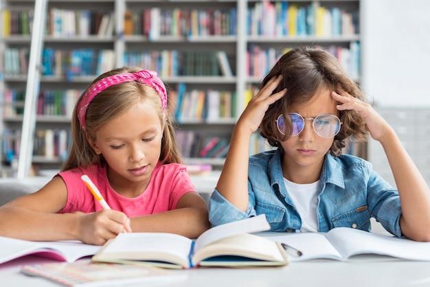図書館で宿題を学び、やっている子供たち
