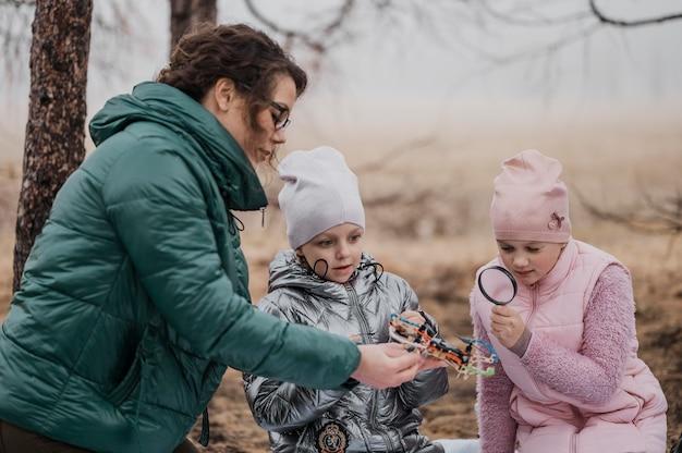 屋外で先生と一緒に新しい科学のことを学ぶ子供たち