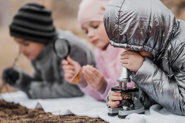 屋外の自然の中で新しいことを学ぶ子供たち