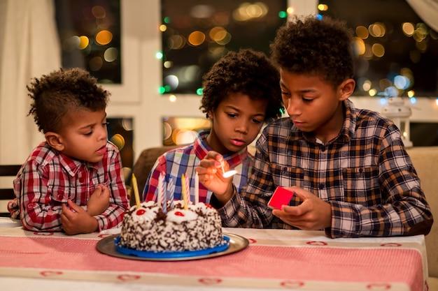子供たちが誕生日ケーキのキャンドルを灯す男の子がケーキの夜の誕生日のお祝いの誕生にキャンドルを灯す...