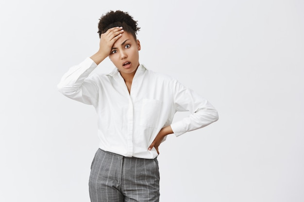 Kids like pain in ass. portrait of displeased and tired sucessful businesswoman in suit, touching forehead and holding hand on waist, coming home and seeing huge mess, being tired and fed up