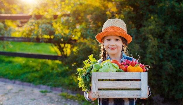 Kids little girl holding a basket of fresh organic vegetables