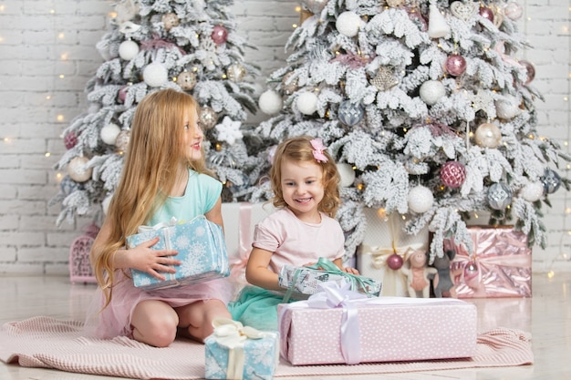 クリスマスのインテリアで美しいファッショナブルな幸せな贈り物を持つ子供たちの小さな女の子の姉妹