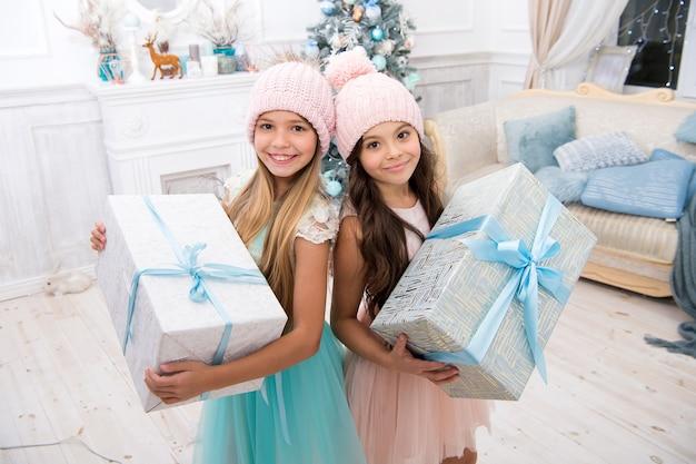 子供の妹は、ギフトボックスのインテリアの背景を保持しています。なんて素晴らしい驚きでしょう。小さなかわいい女の子がホリデーギフトを受け取りました。最高のおもちゃとクリスマスプレゼント。子どもたちの友達は、プレゼントを開梱することに興奮していました。