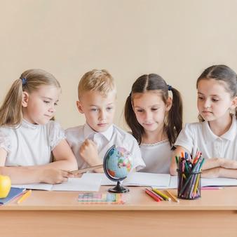 Дети, смотрящие на глобус в школе