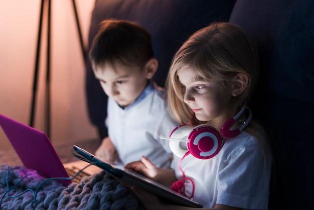 Дети, глядя на планшет и ноутбук