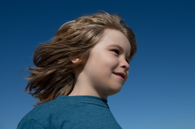 Kids looking away, close up head of cute child on blue sky with copy space.