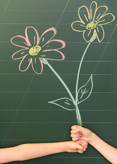 Kids looking like they're holding a bunch of flowers drawn on a blackboard