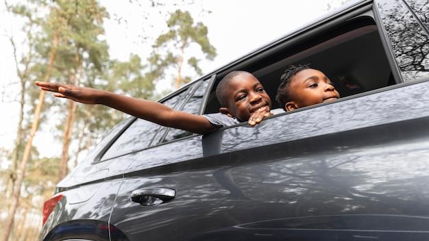 Дети смотрят на улицу через окно машины