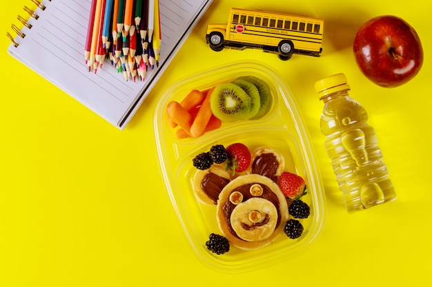 Kids lunch box with pancake, berries, drink and apple on yellow surface