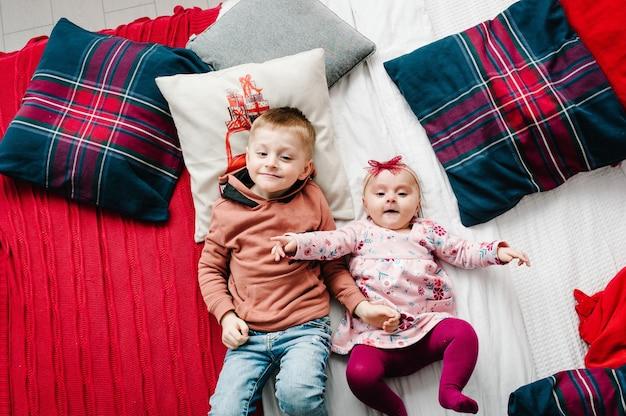 Дети лежат на кровати в спальне возле елки плоский вид сверху концепция семейного отдыха
