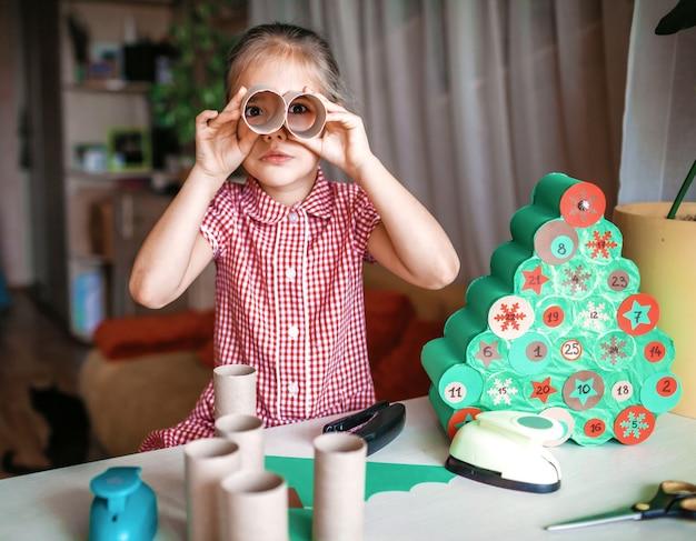 自宅でトイレットペーパーロールで手作りのクリスマスアドベントカレンダーを作る子供たち