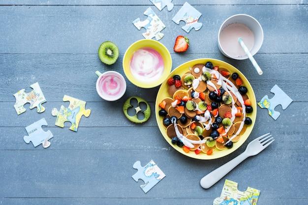 I mini pancake per bambini trattano lo sfondo, la carta da parati con kiwi e frutti di bosco