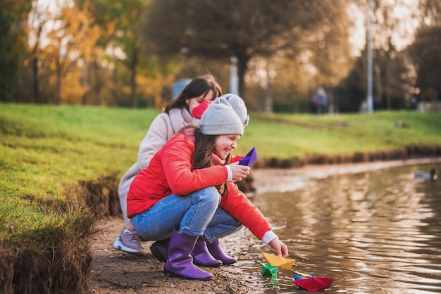 Kids and mother playing with paper boats in lake
