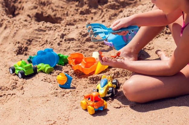 砂で遊んでビーチで子供たち。子供の頃、休暇、夏のコンセプト