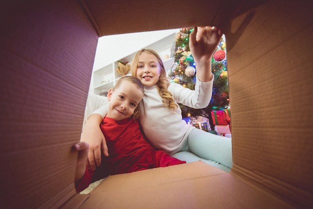 The kids open the box near the christmas tree