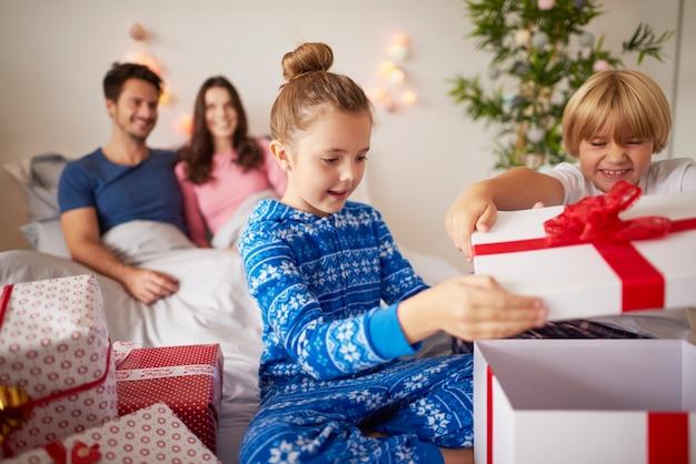 침대에서 크리스마스 선물을 여는 아이들