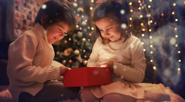 Дети открывают рождественские подарки дети под елкой с подарочными коробками