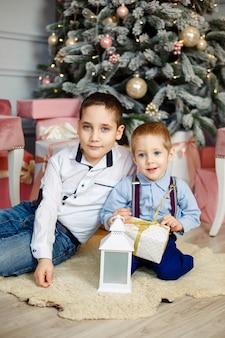 クリスマスプレゼントを開く子供たち。居心地の良い暖かい夜。クリスマスイブの家族