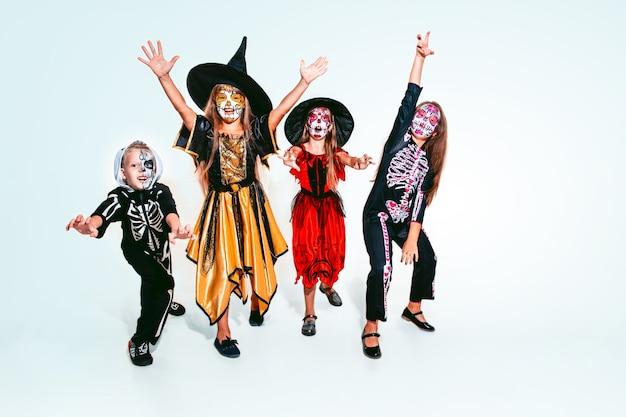 白い背景の白人モデルに骨とキラキラと魔女や吸血鬼のような子供や十代の若者たち