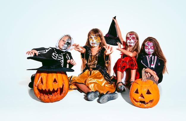 白い背景の白人モデルに骨とカボチャを持つ魔女や吸血鬼のような子供や十代の若者たち