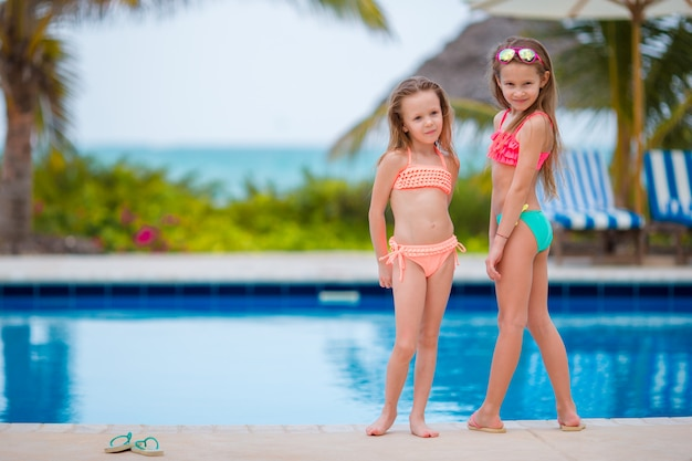 Kids in outdoor swimming pool on summer vacation