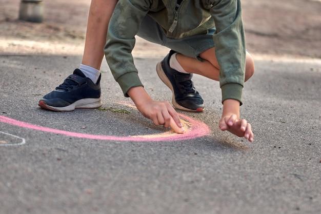 아이들은 야외에서 그림을 그립니다. 아스팔트 놀이터에서 무지개 색 분필을 그리는 소년