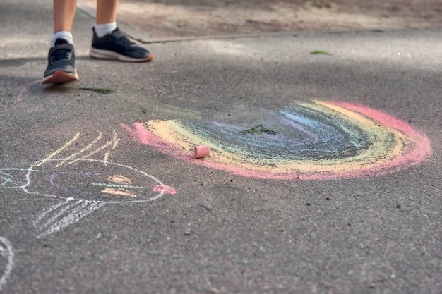 아이들은 야외에서 그림을 그립니다. 여름 화창한 날 아스팔트에 무지개 색 분필을 그리는 어린 소년의 초상화. 아이들은 놀이터에서 놀고 있습니다. 야외 활동
