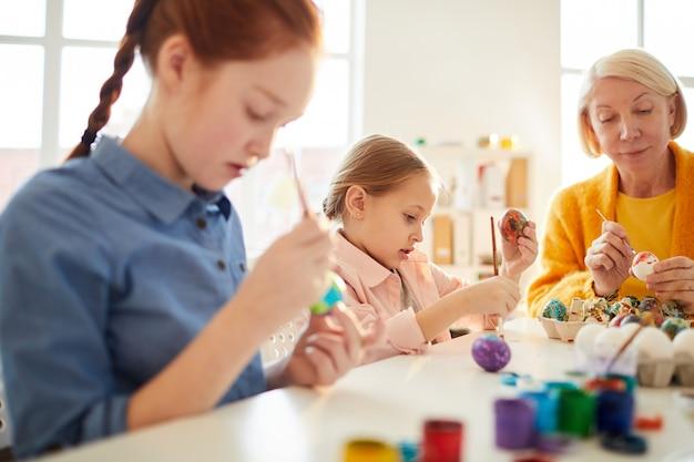 子供たちはイースターのための卵を塗る